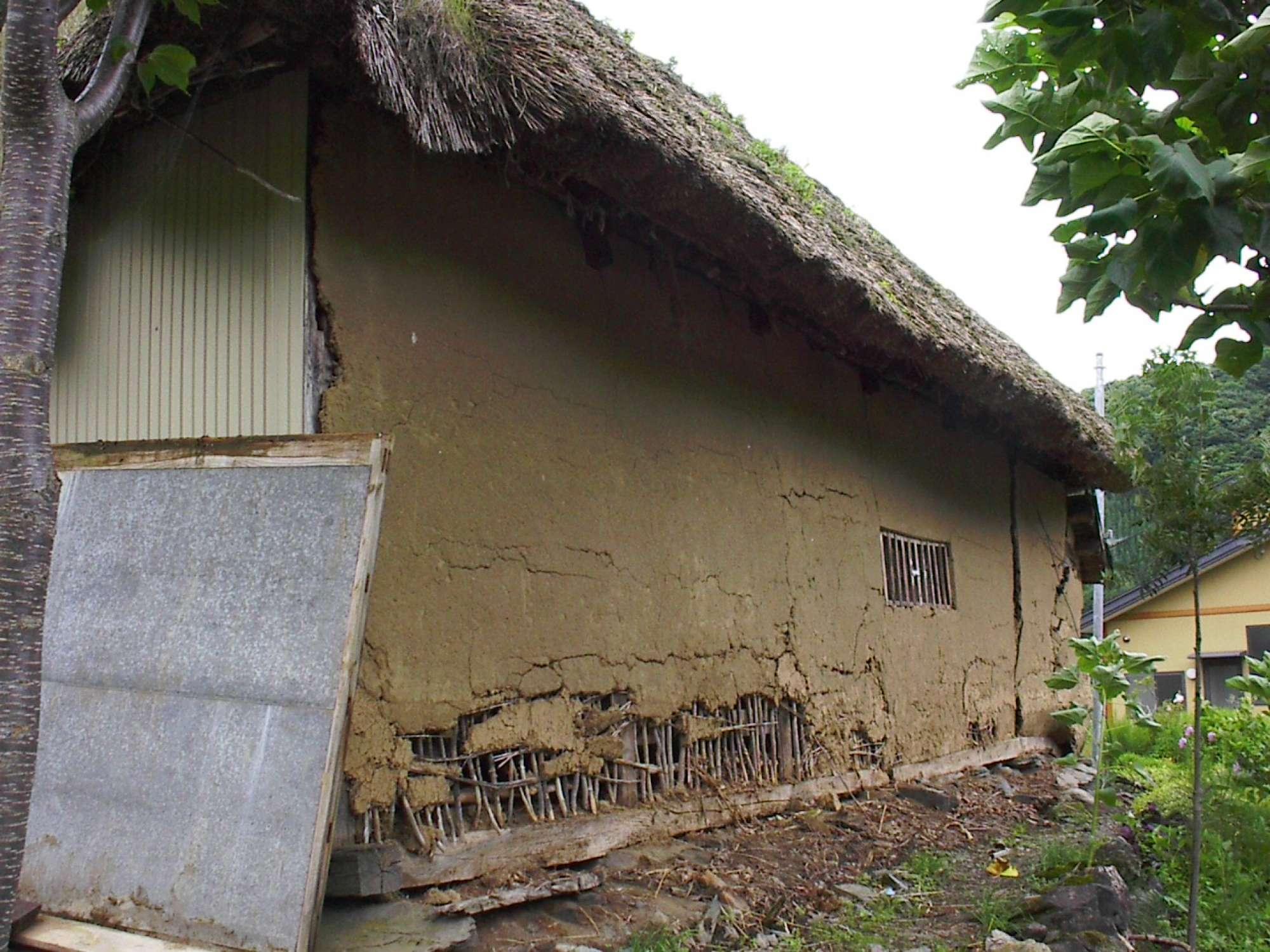 - 土壁+竹細いによる外壁。土壁から下地の竹小舞が見えています。格子状に編み込んで構成された竹に、土を盛って外壁をつくる工法。奥は通風用の窓でしょうか。竹格子のようです。 -  -